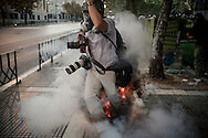 A photographer gets caught under a shock bomb during a protest in Thessaloniki, Greece Sept 11, 2011.  Taxi cab drivers, students and even futbol fans marched and shouted slogans during a protest in opposition of the new higher education draft law. Photo Ken Cedeno