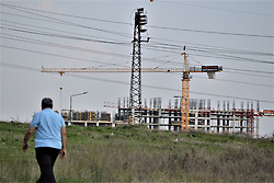 April 13, 2018 - Ankara, Turkey - A man walks past a field, while a residential apartment is seen under construction in Ankara on April 13, 2018. Despite one of the most profitable businesses in Turkey, construction sector now loses its popularity in consequence of the Turkish Lira's continuous depreciation against foreign currency, including the euro, the U.S. dollar and the British pound, in the last months. (Credit Image: © Altan Gocher/NurPhoto via ZUMA Press)