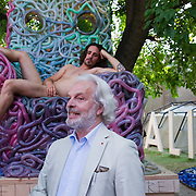 VENICE, ITALY - JUNE 02:    (EDITORS NOTE: Image contains nudity.) Gianni de Luigi  stands in front of actor Massimo Cemolani sited naked on a chair by Gaetano Pesce at the Italian Pavillion on June 2, 2011 in Venice, Italy. This year's Biennale is the 54th edition and will run from June 4th until 27 November.
