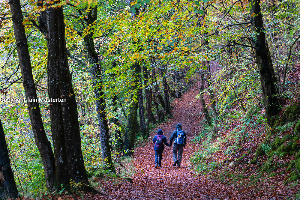 Walkers on footpath in natural woodland on banks of River Garry at historic Pass of Killiecrankie  near Pitlochry.