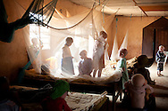 Children play under mosquito netting inside a dormitory of the Kabanga Protectorate Center, housed in a walled compound for the Kabanga Primary School, in Kabanga, Tanzania on Monday, Aug. 27, 2012. The dorms are overcrowded as more people with albinism have been sent to live at the center by the government for their own safety. Having albinism, a genetic condition characterized by a lack of pigment in the body, can be a death sentence in Tanzania. Since 2006 more than 100 people with albinism have been physically attacked in the East African nation, 71 of whom died. Attacks by witch doctors, who use albino body parts in potions said to bring riches, have led the government to place children and adults with albinism into centers for their own safety. Although physically safe they are often stranded in the centers, many over-crowded boarding schools, with little long-term plan for their futures. (photo by Jacquelyn Martin)