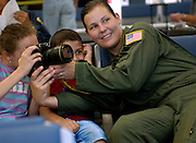 U.S. Air Force Staff Sgt. Stacy Pearsall, from the 1st Combat Camera Sqaudron, shows American children how to capture an image inside the terminal on Ramstein Air Base, Germany, July 22, 2006. The Air Force is flying American citizens who departed Lebanon to the United States. (U.S. Air Force photo by Tech. Sgt. Russell E. Cooley IV) (Released)