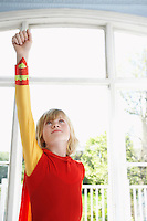 Portrait of young boy (7-9) in superhero costume with raised fist looking up