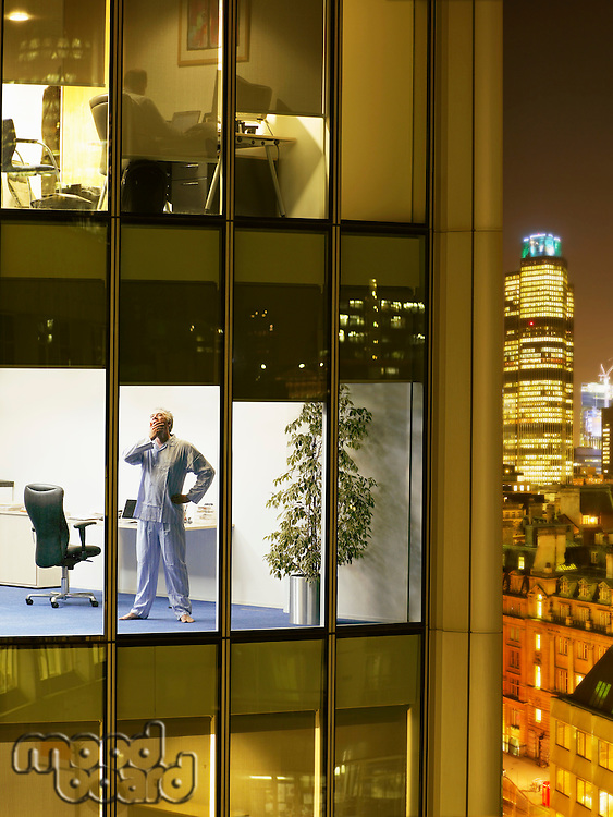 Man wearing pajamas standing in office and yawning view from building exterior