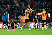 Steve Cook (3) of AFC Bournemouth looks dejected at full time after a 2-1 loss as Raul Jimenez (9) of Wolverhampton Wanderers amd Ruben Vinagre (29) of Wolverhampton Wanderers celebrate the win during the Premier League match between Bournemouth and Wolverhampton Wanderers at the Vitality Stadium, Bournemouth, England on 23 November 2019.