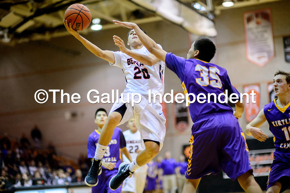 Gallup Bengal Ronald Lee (20), left, extends for a layup around Kirtland Central Bronco Bernel Miller  (35) at Gallup High School Wednesday.