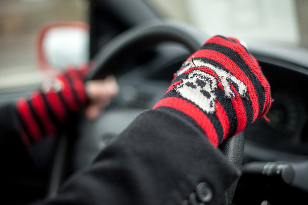 "A man is driving his car with ""skull and bones"" gloves."