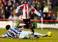 Photo: Leigh Quinnell.<br /> Brentford v Huddersfield Town. Coca Cola League 1. 21/01/2006. Brentfords Issiah Rankin jumps a challenge by Huddersfields  Andy Holdsworth.