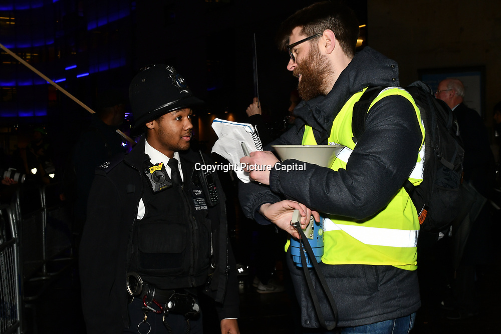 A policeman trying to takes away the mic during BDS Movement with solidarity Palestine to say NO to culture-washing, NO to pink-washing, NO to Eurovision being hosted in Apartheid Israel! counted Pro-Israel outside BBC Broadcasting House, London, UK. 8 Feb 2019.