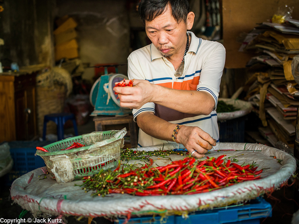 01 APRIL 2014 - BANGKOK, THAILAND: A vendor sorts chilies in the Bangkok flower market. The Yodpiman Flower Market (also called Pak Khlong Talat) is being renovated and gentrified. The market opened in 1961 and has been a Bangkok landmark for more than 50 years, is being turned into a high end mall. Many of the flower and vegetable vendors in the market may be forced out.    PHOTO BY JACK KURTZ