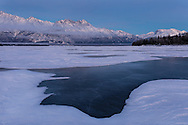 Dusk descends over the Chugach Mountains and the Knik River in Southcentral Alaska. Winter. Afternoon.