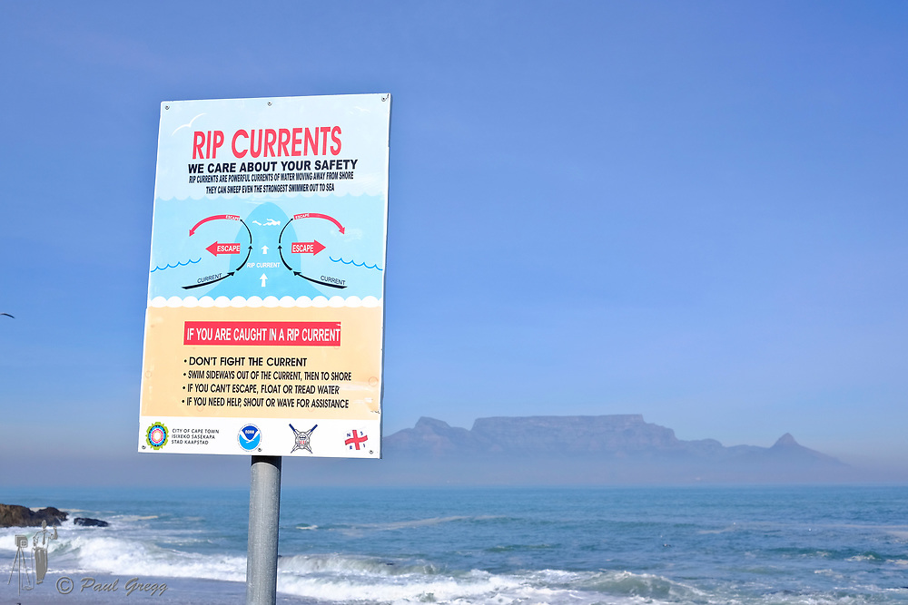 Table Mountain,Cape Town, South Africa. A rip current advisory sign posted on the beach at Bloubergstrand. A blanket of smog covers the base of Table Mountain in the early winter morning.