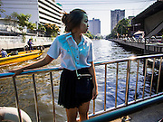 19 JANUARY 2015 - BANGKOK, THAILAND: A woman rides across Khlong Saen Saeb on the ferry. The small ferry crosses Khlong Saen Saeb throughout the day. It is powered by an diesel engine that uses a system of cables to pull the ferry the 30 feet across the canal. It's used by pedestrians  who need to get across the khlong. The nearest bridge is about ½ mile away.     PHOTO BY JACK KURTZ