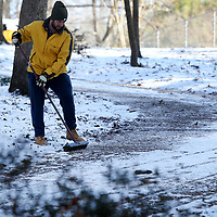 Russell Johnson, of Tupelo, sweeps his steep driveway after using a seed spreader to spread salt at his home on Rachel Street in the Oakcliff Villas neighborhood in east Tupelo to try and speed up the process of melting the ice so his wife will be able to leave for work later in the day.
