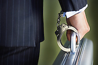 Middle-aged businessman handcuffed to briefcase mid section close-up back view