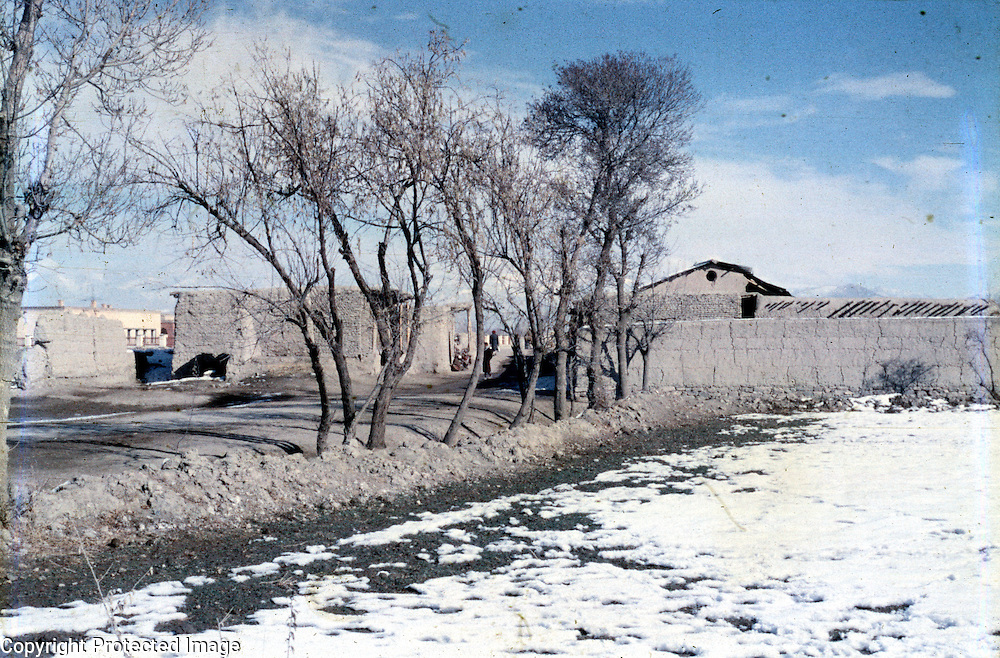 8 January 1963<br /> Kabul Buthkhak Village - K9 &gt; K15 First Tajik Village LD.<br /> Buthkhak village outside Kabul. Local village houses, Unpaved road, Trees and Stream on right side of the road, Snow covered fields.
