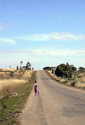 A woman walking along one of the few paved roads in Madagascar. From Ihosy to Fianarantsoa