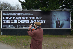 "© Licensed to London News Pictures. 25/02/2013. Eastleigh, UK. A man takes a picture after Brian Leggett, UK spokesperson for the International Consortium of British Pensioners  (ICBP) launches a billboard campaign in Eastleigh, Hampshire, today 25th February 2013. the ""How Can We Trust The Lib Dems Again"" claims that pensioners who live abroad are unlikely to receive their full state pensions. Photo credit : Stephen Simpson/LNP"