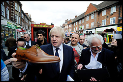 London Mayor Boris Johnson is given a new pair of shoes while campaigning in .Golders Green, London, UK, April 15, 2012. Photo By Andrew Parsons / i-Images.