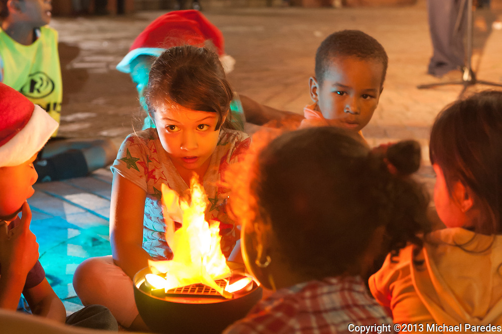 A young girl talks with her friends in front of artificial firelight in the Casco Viejo neighborhood of Panama City, Panama