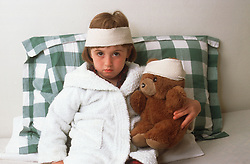 Young girl with bandaged head holding bandaged teddy bear,