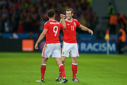 5LILLE, FRANCE - Friday, July 1, 2016: Wales' Gareth Bale celebrates the second goal with goalscorer Hal Robson-Kanu during the UEFA Euro 2016 Championship Quarter-Final match  against Belgium at the Stade Pierre Mauroy. (Pic by Paul Greenwood/Propaganda)