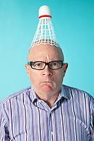 Portrait of angry man with shuttlecock on head over colored background