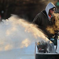 Joel Lange's breath is visible while he clears the sidewalk along Phillips Avenue Friday, Jan. 9, 2015.