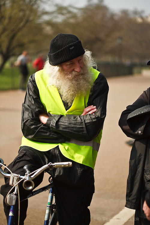 A man on a bicycle stops to listen at Speaker's Corner in Hyde Park, London, England.