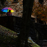 A woman holds an umbrella on a rainy day amidst fall colors at the Glade Creek Grist Mill inside Babcock State Park near Clifftop, W.Va., on Saturday, October 27, 2018.