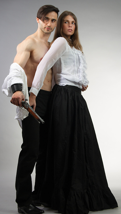 Couple posing together in historical outfits.