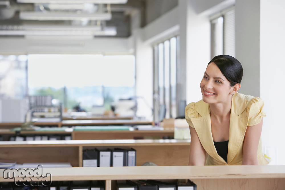 Woman sitting at desk in office smiling
