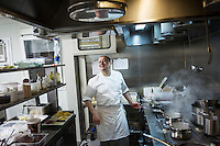 "MILANO, ITALY - 1 MARCH 2016: Mirko Savoldelli, an Italian inmate and cook, jokes with other inmates as he prepares a risotto for customers in the kitchen of the ""InGalera"" restaurant at the Bollate prison in Milan, Italy, on March 1st 2016.<br /> <br /> ""InGalera"" (which translates in English as ""InJail"") is the first restaurant located inside a prison and offering high-quality cooking to the public and a future to the inmates. It was inaugurated last October inside the Bollate prison in Milan. It is open five days a week for lunch and dinner, and seats 55 people. There are 9 people involved in the project, including cooks and waiters, all regularly employed and all inmates of the prison, apart from the chef and the maître d'hôtel, recruited from outside to guarantee the high quality of the food served. The restaurant is a project of the co-operative ABC La Sapienza - that operates inside the prison and provides more than 1,000 meals three times a day with the help of inmates they've hired - and of PwC, a multinational operating in the field of corporate consultancy. The goal of this project is to follow prisoners in rehabilitation process of social inclusion.<br /> <br /> The Bollate prison is already known for being a good example of penitentiary administration. The inmates are free to move around from one area to the other inside the prison (their cells open at 7:30am and close at 9pm) to go study, exercise in a gym, or work (in a call center, as scenographers, tailors, gardeners, cooks, typographers, among others)  in one of the 11 co-operatives inside the prison or in one of the private partnering businesses outside the prison. The turnover of the co-operatives that work inside the prison was €2mln in 2012."