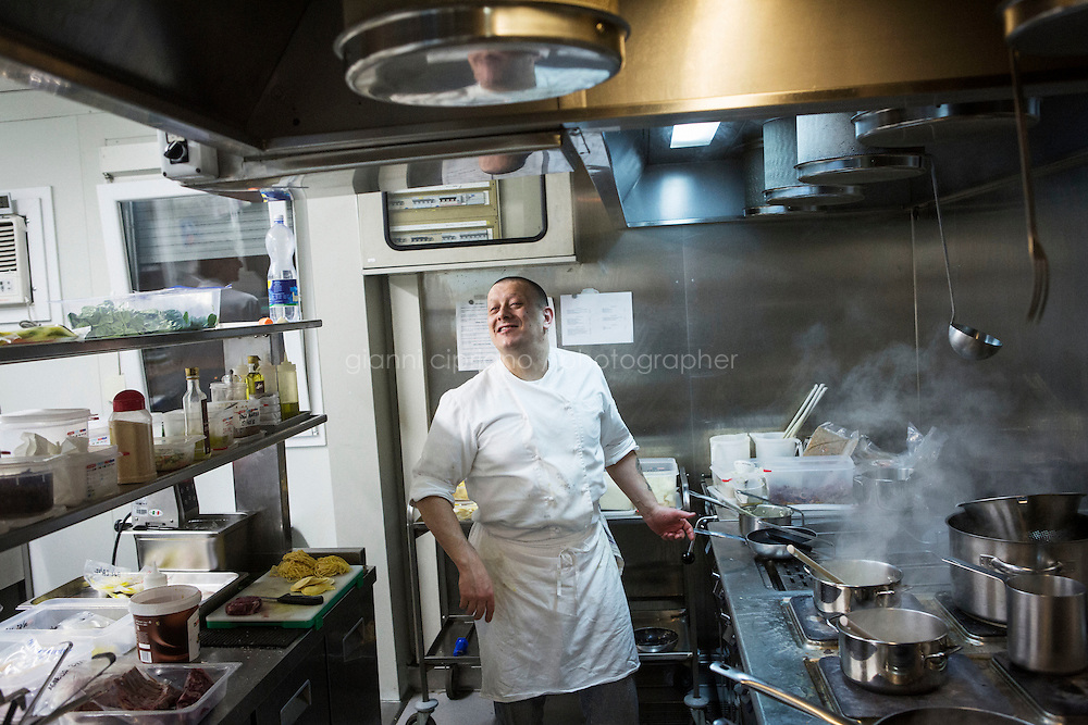 """MILANO, ITALY - 1 MARCH 2016: Mirko Savoldelli, an Italian inmate and cook, jokes with other inmates as he prepares a risotto for customers in the kitchen of the """"InGalera"""" restaurant at the Bollate prison in Milan, Italy, on March 1st 2016.<br /> <br /> """"InGalera"""" (which translates in English as """"InJail"""") is the first restaurant located inside a prison and offering high-quality cooking to the public and a future to the inmates. It was inaugurated last October inside the Bollate prison in Milan. It is open five days a week for lunch and dinner, and seats 55 people. There are 9 people involved in the project, including cooks and waiters, all regularly employed and all inmates of the prison, apart from the chef and the maître d'hôtel, recruited from outside to guarantee the high quality of the food served. The restaurant is a project of the co-operative ABC La Sapienza - that operates inside the prison and provides more than 1,000 meals three times a day with the help of inmates they've hired - and of PwC, a multinational operating in the field of corporate consultancy. The goal of this project is to follow prisoners in rehabilitation process of social inclusion.<br /> <br /> The Bollate prison is already known for being a good example of penitentiary administration. The inmates are free to move around from one area to the other inside the prison (their cells open at 7:30am and close at 9pm) to go study, exercise in a gym, or work (in a call center, as scenographers, tailors, gardeners, cooks, typographers, among others)  in one of the 11 co-operatives inside the prison or in one of the private partnering businesses outside the prison. The turnover of the co-operatives that work inside the prison was €2mln in 2012."""