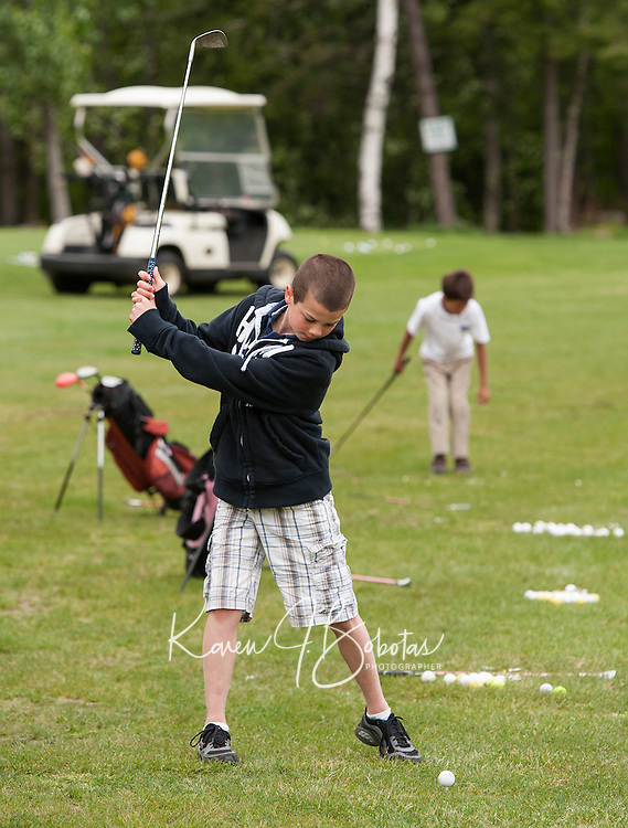 Eric Phelps practices his swing during his golf lesson with Randy Annis at Bolduc Park Tuesday evening.  (Karen Bobotas/for the Laconia Daily Sun)