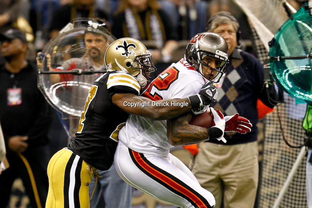 November 6, 2011; New Orleans, LA, USA; Tampa Bay Buccaneers tight end Kellen Winslow (82) is tackled by New Orleans Saints safety Malcolm Jenkins (27) during the first quarter of a game at the Mercedes-Benz Superdome. Mandatory Credit: Derick E. Hingle-US PRESSWIRE