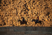 Two horse riders in the shade in front of a pyramid in Giza, Egypt.