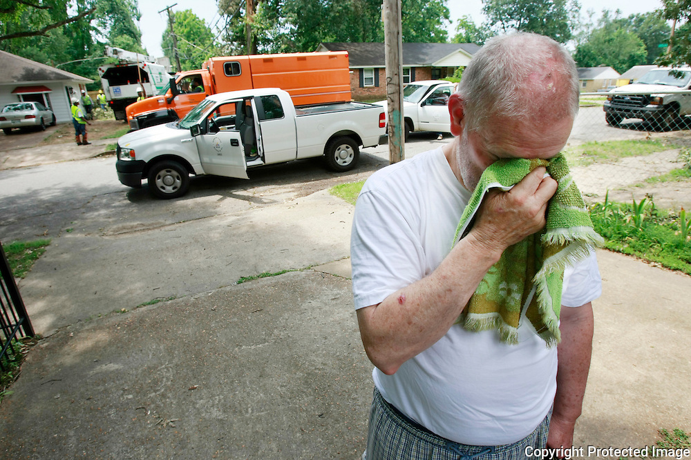 """16 June 09 (kpnopow1) by Karen Pulfer Focht: Jerry Lynn Smith waits patiently in his driveway for his lights to come back on. He wiped his sweat,Tuesday, moments before his power to his air conditioner was restored. """"It makes for long nights"""" he said of the heat and no power.  His neighborhood near Jackson and Wales has been without power since Friday. His power was turned on shortly after noon. The other homes nearby were still going to be without power today. (3960 Pikes Peak)"""