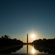 The sun low on the horizon soon after sunrise behind the Washington Monument and Lincoln Memorial Reflecting Pool on the National Mall in Washington DC. Around the equinox, the sun rises directly to the east, lining up with the monuments on the Mall.