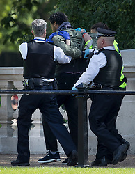 © Licensed to London News Pictures. 24/05/2017. London, UK. Police remove a man they detained opposite Buckingham Palace just before the Changing of the Guard ceremony was due to take place. Today's ceremony has been cancelled.  The terrorism threat level has been raised to critical and Operation Temperer has been deployed. 5,000 troops are taking over patrol duties under police command. Photo credit: Peter Macdiarmid/LNP