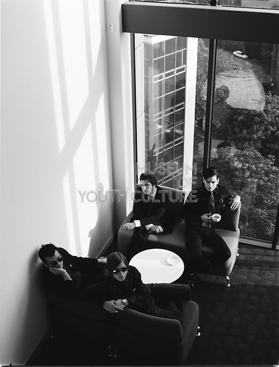 Four young men sitting on sofas dressed in black.
