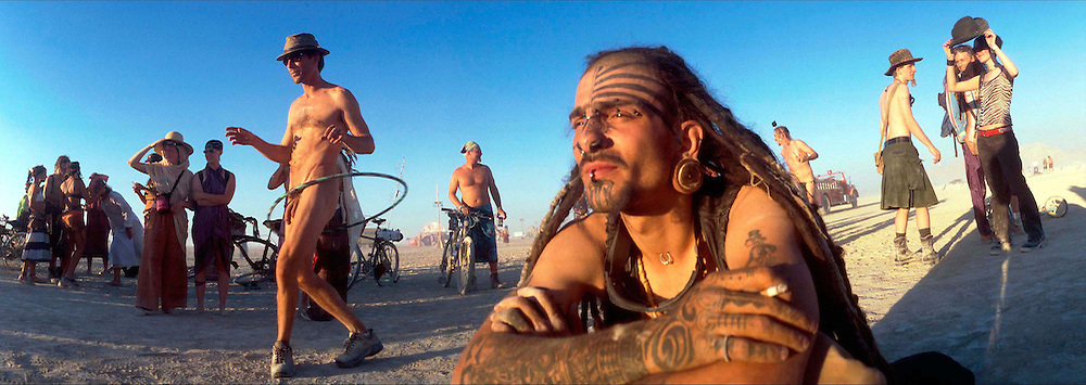 """Citizens of Black Rock City watch the sun set August 27, 2001 at the 16th annual Burning Man festival in the Black Rock Desert near Gerlach, Nevada. An estimated record 29,000 people camped out on a remote desert playa, or dry lake, for the week-long counter-cultural celebration of art and """"radical self-expression."""" This year's theme was the stages of man."""
