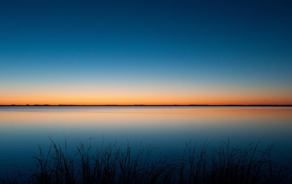 Dawn sunrise glow on the eastern horizon over the lake at Cheyenne Bottoms Wildlife area, Kansas