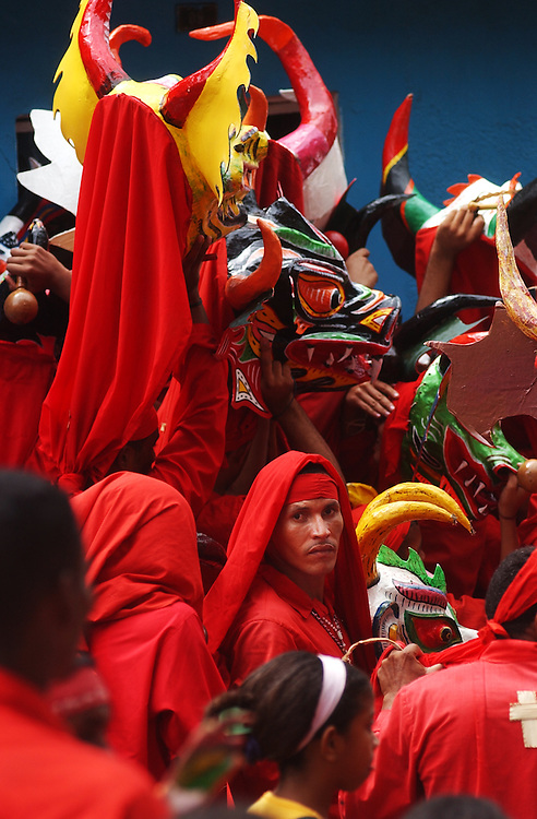 Devil Dancers(Los Diablos Danzantes) cram to get into a home and dance during the Corpus Christi celebration.  Venezuela is dotted with towns that celebrate Corpus Christi with a two day devil dancing celebration.  Community members, dressed as devils, first dance in front of the Church asking for forgiveness from their sins.  They then parade through the town dancing making stops at a various homes along the way.  The houses all have stands with religious symbols and candles inf front of which  the Devil Dancers pray and beg forgiveness    It is considered an honor to dance during the celebration.