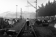 08 March 2016, Idomeni Greece - A refugee woman walks along the railroad tracks near the station Idomeni, occupied by the tents of refugees.