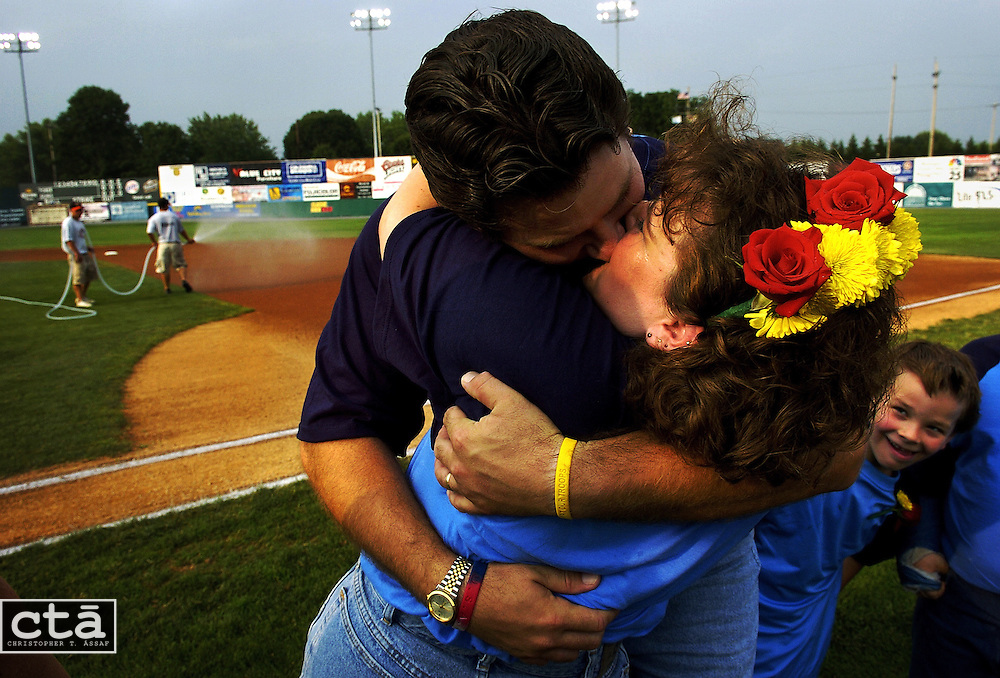 """I didn't do so well the first time,"" Robert Smith said after giving his wife, Karen, a big kiss after renewing their vows before a Hagerstown Sun baseball game. The Hagerstown couple has been married 15 years and have three children, including 7-year-old Michael (R) who seems surprised at his parent's smooch. Five couples participated in Renew Your Vows night at the minor league ball park."