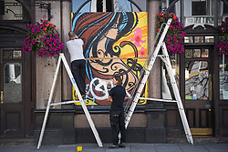 © Licensed to London News Pictures. 23/08/2019. London, UK. Graffiti covered boards being erected around a pub  ahead of the 2018 Notting Hill Carnival which starts this weekend. Warm weather is expected over the bank holiday weekend with carnival attracting over 1 million people to the capital. Photo credit: Ben Cawthra/LNP