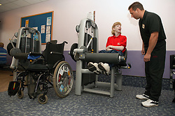 Access to services, Fitness instructor with disabled woman in the gym; using Leg Extension,