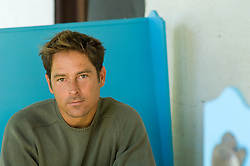 Man in a green sweater on a  blue bench