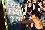"September 25, 2010 - Samantha Kattan writes on a sandwich board at the 5th Fluff Fest, which was held this past Saturday in Somerville. She said that her favorite thing about Fluff was, ""the nostalgic kind of silly luxury that makes people happy."" Photo by Lathan Goumas."